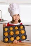Το υπερήφανο κορίτσι που παρουσιάζει μόνο γίνοντα muffin της συσσωματώνει το ψήσιμο εκμάθησης φορώντας την κόκκινη ποδιά και μαγε Στοκ Εικόνες