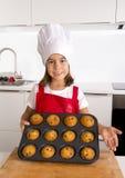 Το υπερήφανο κορίτσι που παρουσιάζει μόνο γίνοντα muffin της συσσωματώνει το ψήσιμο εκμάθησης φορώντας την κόκκινη ποδιά και μαγε Στοκ εικόνα με δικαίωμα ελεύθερης χρήσης