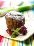 Muffin. Chocolate muffin with marmalade on a colorful cover Royalty Free Stock Image