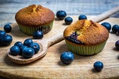 Muffin ai mirtilli con i mirtilli sui cucchiai di legno e sulla b di legno Fotografie Stock
