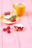 Muffin al forno casalingo con i lamponi, le bacche fresche, la menta sul piatto e la tazza di caffè su fondo di legno rosa Fotografie Stock