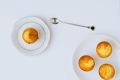 Muffin arancio in piatti bianchi su un fondo bianco Fotografia Stock