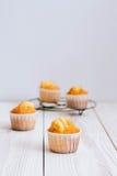 Muffin arancio su un fondo di legno bianco Fotografia Stock