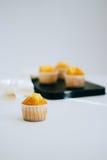 Muffin arancio su un vassoio d'annata del metallo Immagini Stock