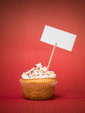 Muffin with banner. Muffin with colorful candy on the table red with white dots and blank sign board gradient red background Stock Photos