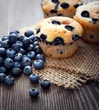 Muffin with blueberries on a wooden table. fresh berries and swe. Et pastries on the board stock images