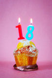 Muffin with burning birthday candles as number eighteen Royalty Free Stock Image