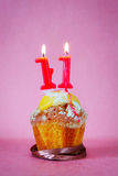 Muffin with burning birthday candles as number eleven. On pink background stock photos