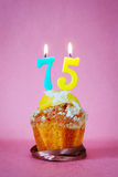 Muffin with burning birthday candles as number seventy five. On pink background Royalty Free Stock Photo