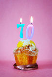 Muffin with burning birthday candles as number seventy. On pink background Stock Photo