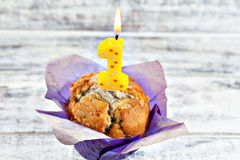 Muffin with burning candle. Homemade blueberry muffin wrapped in paper with burning one shaped yellow candle. Top point of view Stock Image