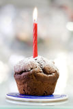 Muffin and Candle. A tasty chocolate muffin with candle isolated on color background. Candle at focus and shallow depth of field Stock Photo