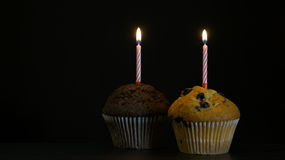 Muffin with a candle close up on black background. Muffin with a candle close up on a black background Royalty Free Stock Photo