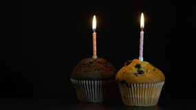 Muffin with a candle close up on black background. Muffin with a candle close up on a black background Stock Image