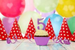 Muffin with candle in number 5 shape. And party hats in the background Stock Image