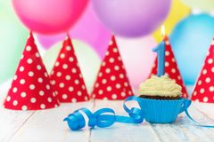 Muffin with candle and party hats. Birthday muffin with candle and party hats in the background Stock Photo