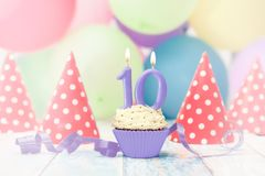 Muffin with candle for tenth birthday. With blue ribbon and party hats on the table Stock Image