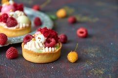 Muffin casalinghi con crema dolce ed i lamponi rossi e gialli freschi su una fine confusa grigia del fondo su Fotografia Stock Libera da Diritti