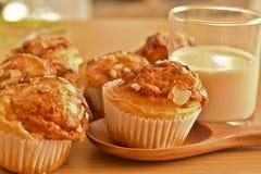 Muffin casalinghi deliziosi della mandorla e un bicchiere di latte su di legno Fotografia Stock