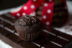 Muffin and chocolate chip cookie with chocolate bar and red silk bow with white dots Stock Photography