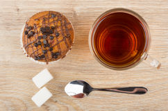 Muffin with chocolate, cup of tea, lumpy sugar and spoon Royalty Free Stock Photos