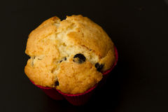 Muffin. A closeup image of a baked muffin in a red cup against a dark background stock images