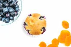 Muffin con il tiro sopraelevato delle albicocche e dei mirtilli Fotografia Stock