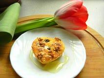 Muffin con miele su un piatto e su un tulipano bianchi Fotografie Stock