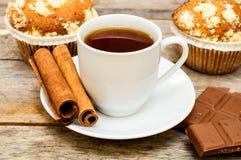 Muffin con tè, i bastoni di cannella ed il cioccolato Fotografia Stock