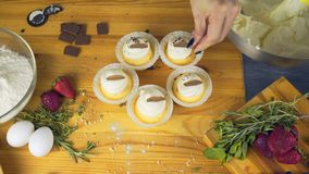Muffin with cream and chocolate chips on top of him sits on a bright wooden table.  stock footage