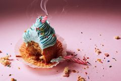 Muffin with cream and extinguished candle. the concept of the end of the celebration.  Royalty Free Stock Image