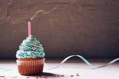 Muffin with cream and extinguished candle. the concept of the end of the celebration.  Stock Image