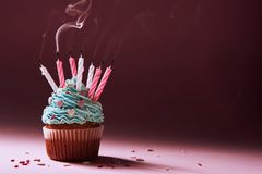 Muffin with cream and extinguished candle. the concept of the end of the celebration. Muffin with cream and extinguished candle. the concept of the end of the Stock Images