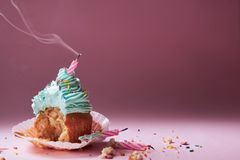 Muffin with cream and extinguished candle. the concept of the end of the celebration.  Stock Photo