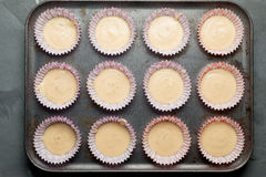 Muffin Cups with Cake Batter in Baking Tray. Muffin cups with cake batter arranged in baking tray overhead stock photo