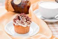 Muffin with custard cream and coffee. daylight. Beige background, morning sun at breakfast Stock Images