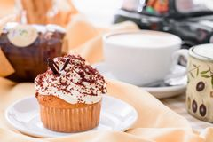Muffin with custard cream and coffee. daylight. Beige background, morning sun at breakfast Stock Photos