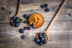 Muffin de blueberry com os mirtilos em colheres de madeira e em b de madeira foto de stock