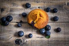 Muffin de blueberry com os mirtilos em colheres de madeira e em b de madeira fotografia de stock royalty free