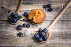 Muffin de blueberry com os mirtilos em colheres de madeira e em b de madeira fotografia de stock