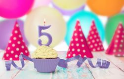 Muffin decorated with candle and ribbon. Muffin decorated with number 5 candle and purple ribbon Stock Photos