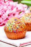 Muffin decorated with sprinkles on pink napkin. Royalty Free Stock Images