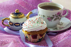 Muffin, decorated with whipped protein cream, on the background cup of  tea  and teapot Royalty Free Stock Photo