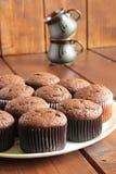 Muffin del cioccolato su un piatto e sulle tazze Immagini Stock Libere da Diritti
