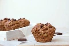 Muffin del cioccolato sui precedenti bianchi e rosa Immagine Stock