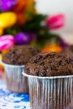Muffin del cioccolato sui precedenti dei tulipani Fotografia Stock