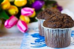Muffin del cioccolato un giorno del ` s della madre nei precedenti dei fiori Immagini Stock Libere da Diritti
