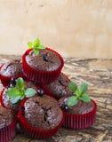 Muffin di recente al forno del cioccolato con il ribes e la menta nelle forme rosse Fotografie Stock