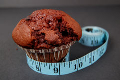 Muffin Diet 2. This is an image a chocolate muffin and a measuring tape. This is a metaphor for dieting. (Please let me know where the image will be used by stock image