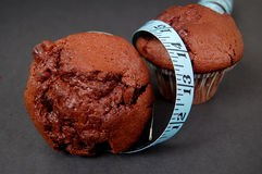 Muffin Diet 3. This is an image of two chocolate muffins and a measuring tape. This is a metaphor for dieting. (Please let me know where the image will be used stock image